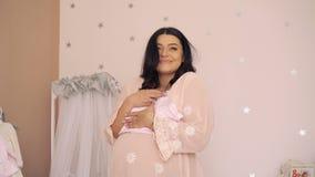 Έγκυος γυναίκα που κοιτάζει στα ενδύματα σε ένα τρυφερό μελλοντικό δωμάτιο μωρών 4K απόθεμα βίντεο
