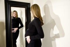 Έγκυος γυναίκα που κοιτάζει στον καθρέφτη Στοκ εικόνα με δικαίωμα ελεύθερης χρήσης