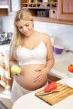 Έγκυος γυναίκα που κρατά την πράσινη Apple και το χαμόγελο Στοκ Εικόνα