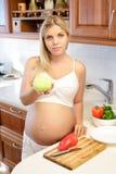 Έγκυος γυναίκα που κρατά την πράσινη Apple και το χαμόγελο Στοκ φωτογραφίες με δικαίωμα ελεύθερης χρήσης