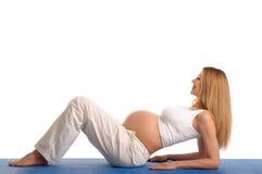 Έγκυος γυναίκα που ξαπλώνει και γιόγκα άσκησης στοκ φωτογραφία με δικαίωμα ελεύθερης χρήσης
