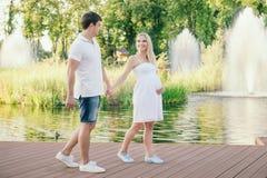 Έγκυος γυναίκα που περπατά με το σύζυγο στην αποβάθρα κοντά στο νερό Στοκ εικόνα με δικαίωμα ελεύθερης χρήσης