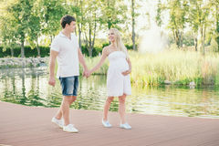 Έγκυος γυναίκα που περπατά με το σύζυγο στην αποβάθρα κοντά στο νερό Στοκ Εικόνες