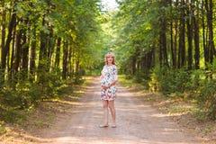 Έγκυος γυναίκα που περπατά στο πάρκο και που αγκαλιάζει την έγκυο κοιλιά της Στοκ Φωτογραφία