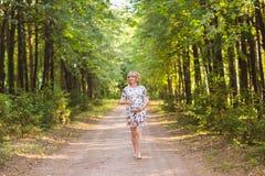 Έγκυος γυναίκα που περπατά στο πάρκο και που αγκαλιάζει την έγκυο κοιλιά της Στοκ Εικόνες