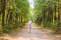 Έγκυος γυναίκα που περπατά στο πάρκο και που αγκαλιάζει την έγκυο κοιλιά της Στοκ φωτογραφία με δικαίωμα ελεύθερης χρήσης