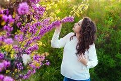 Έγκυος γυναίκα που περπατά την άνοιξη το πάρκο Με ένα χέρι που αγκαλιάζει την κοιλιά και αγγίζει τα λουλούδια με άλλο, κοιτάζει Στοκ Εικόνα