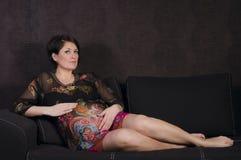 Έγκυος γυναίκα που στηρίζεται στον καναπέ Στοκ Εικόνες