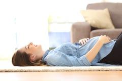 Έγκυος γυναίκα που στηρίζεται στο πάτωμα στο σπίτι στοκ φωτογραφία με δικαίωμα ελεύθερης χρήσης