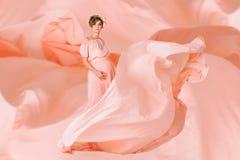 Έγκυος γυναίκα που χορεύει στο ρόδινο φόρεμα βραδιού που πετά στον αέρα Κυματίζοντας ύφασμα, πυροβολισμός μόδας Στοκ φωτογραφίες με δικαίωμα ελεύθερης χρήσης