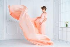Έγκυος γυναίκα που χορεύει στο ρόδινο φόρεμα βραδιού που πετά στον αέρα Κυματίζοντας ύφασμα, πυροβολισμός μόδας Στοκ Φωτογραφίες