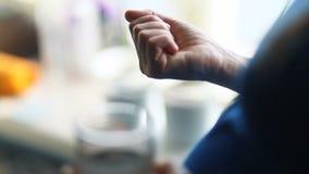 Έγκυος γυναίκα στη μπλε ζακέτα που πίνει παίρνοντας τα φάρμακα φαρμάκων χαπιών που πλένουν στο σπίτι επάνω με το ποτήρι του νερού απόθεμα βίντεο