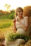 Έγκυος γυναίκα στη φύση κοντά στις θυμωνιές χόρτου Στοκ εικόνα με δικαίωμα ελεύθερης χρήσης