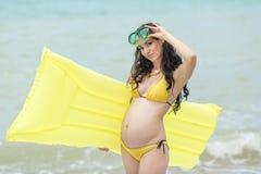 Έγκυος γυναίκα στο κίτρινο μπικίνι στην παραλία Στοκ Εικόνες