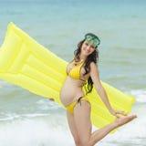 Έγκυος γυναίκα στο κίτρινο παιχνίδι μπικινιών στην παραλία Στοκ Εικόνες