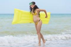 Έγκυος γυναίκα στο κίτρινο παιχνίδι μπικινιών στην παραλία Στοκ Φωτογραφίες