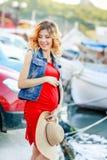 Έγκυος γυναίκα στο κόκκινο πουκάμισο, το καπέλο, τα γυαλιά ηλίου και το μαύρο παντελόνι στη μαρίνα γιοτ της Μάλτας στοκ εικόνες