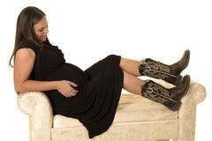 Έγκυος γυναίκα στο μαύρο φόρεμα και μπότες που κάθονται στον καναπέ Στοκ εικόνα με δικαίωμα ελεύθερης χρήσης