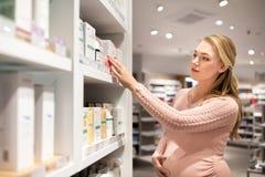 Έγκυος γυναίκα στο φαρμακείο ή το κατάστημα καλλυντικών στοκ φωτογραφία με δικαίωμα ελεύθερης χρήσης