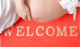 Έγκυος γυναίκα στο wellcome-τάπητα Στοκ Εικόνες