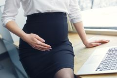 Έγκυος επιχειρησιακή γυναίκα που εργάζεται στη συνεδρίαση μητρότητας γραφείων στην κινηματογράφηση σε πρώτο πλάνο γραφείων στοκ εικόνες