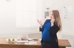 Έγκυος επιχειρησιακή γυναίκα που μιλά στο τηλέφωνο στο γραφείο Στοκ Εικόνες