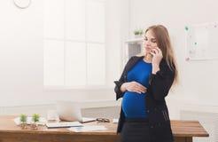 Έγκυος επιχειρησιακή γυναίκα που μιλά στο τηλέφωνο στο γραφείο Στοκ εικόνα με δικαίωμα ελεύθερης χρήσης