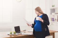 Έγκυος επιχειρησιακή γυναίκα που μιλά στο τηλέφωνο με το φλυτζάνι Στοκ εικόνες με δικαίωμα ελεύθερης χρήσης