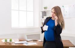 Έγκυος επιχειρησιακή γυναίκα που μιλά στο τηλέφωνο με το φλυτζάνι Στοκ φωτογραφίες με δικαίωμα ελεύθερης χρήσης
