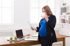 Έγκυος επιχειρησιακή γυναίκα που μιλά στο τηλέφωνο με το φλυτζάνι Στοκ φωτογραφία με δικαίωμα ελεύθερης χρήσης