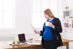 Έγκυος επιχειρησιακή γυναίκα που μιλά στο τηλέφωνο με το φλυτζάνι Στοκ Φωτογραφίες