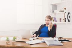 Έγκυος επιχειρησιακή κυρία στην εργασία που μιλά στο τηλέφωνο Στοκ εικόνες με δικαίωμα ελεύθερης χρήσης