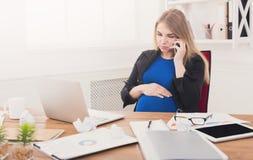 Έγκυος επιχειρησιακή κυρία στην εργασία που μιλά στο τηλέφωνο Στοκ φωτογραφίες με δικαίωμα ελεύθερης χρήσης