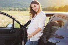 Έγκυος ευτυχής νέα γυναίκα κοντά στο μαύρο αυτοκίνητο Στοκ Εικόνες