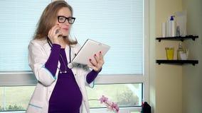Έγκυος θηλυκός γιατρός που μιλά στο τηλέφωνο και που χρησιμοποιεί τον υπολογιστή ταμπλετών από κοινού απόθεμα βίντεο