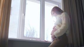 Έγκυος κυρία που κτυπά γυμνό μεγάλο tummy της και που εξετάζει έξω το παράθυρο στο backlight το σπίτι απόθεμα βίντεο