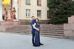 Έγκυος κόκκινη γυναίκα τρίχας στο πολύ μπλε φόρεμα και μοντέρνος άνδρας Στοκ Φωτογραφίες