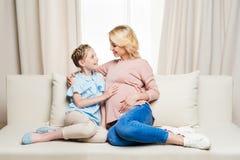 Έγκυος μητέρα με χαριτωμένο λίγη συνεδρίαση κορών μαζί στον καναπέ και χαμόγελο του ενός τον άλλον Στοκ εικόνες με δικαίωμα ελεύθερης χρήσης