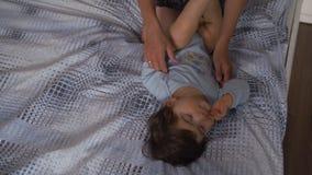 Έγκυος μητέρα που βάζει με το γιο μωρών της στο κρεβάτι κρεβατοκάμαρων που παίζει και που έχει τη διασκέδαση - ασιατικό μικτό αγό απόθεμα βίντεο