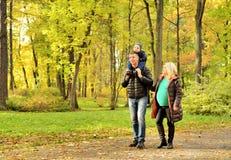 Έγκυος νέα γυναίκα που περπατά στο πάρκο φθινοπώρου με το σύζυγο και το παιδί της στοκ εικόνα με δικαίωμα ελεύθερης χρήσης