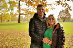 Έγκυος νέα γυναίκα στο πάρκο φθινοπώρου με το σύζυγό της στοκ εικόνα με δικαίωμα ελεύθερης χρήσης