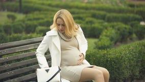 Έγκυος ξανθή γυναίκα που παίρνει το χάπι, καθμένος στον πάγκο πάρκων, που αισθάνεται τον κοιλιακό πόνο απόθεμα βίντεο
