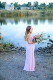 Έγκυος ξανθή γυναίκα που φορά το ρόδινο φόρεμα με την ανθοδέσμη των λουλουδιών που στέκονται κοντά στη λίμνη Στοκ Εικόνες