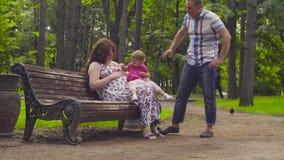 Έγκυος συνεδρίαση mom και κοριτσάκι σε έναν πάγκο απόθεμα βίντεο
