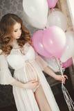 Έγκυος όμορφη γυναίκα με τη δέσμη των μπαλονιών Στοκ Εικόνες
