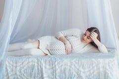 Έγκυος όμορφη γυναίκα που βρίσκεται στο κρεβάτι θόλων Φθορά του άσπρων πλεκτών πουλόβερ και των γυναικείων καλτσών στοκ εικόνες