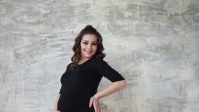 Έγκυος moman κάθεται στα σκαλοπάτια Πρότυπο που ντύνεται στο μαύρο κομπινεζόν Έβαλε το χέρι της στην κοιλιά μελλοντική ευτυχής μη απόθεμα βίντεο