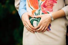 Έγκυο ζεύγος που κάνει τη μορφή καρδιών με τα χέρια στην κοιλιά στο πάρκο υπαίθρια Στοκ Εικόνα