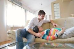 Έγκυο ζεύγος που χρησιμοποιεί στο σπίτι τον υπολογιστή ταμπλετών στοκ φωτογραφία με δικαίωμα ελεύθερης χρήσης