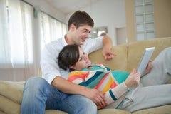 Έγκυο ζεύγος που χρησιμοποιεί στο σπίτι τον υπολογιστή ταμπλετών στοκ εικόνα με δικαίωμα ελεύθερης χρήσης